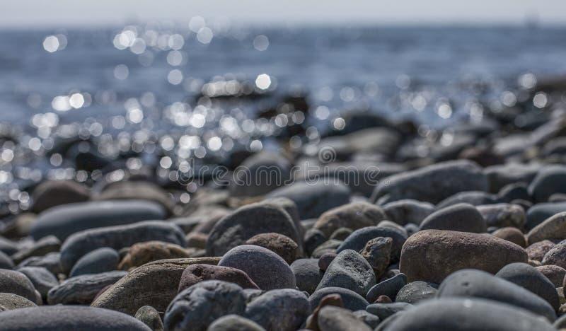 Llanbedrog, Gales, o Reino Unido - as pedras e as águas brilhantes fotos de stock