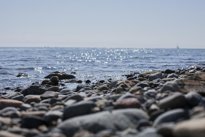 Llanbedrog, Wales, the UK - pebbles and blue shiny waters on a sunny day. This image a beach in LLanbedrog, North Wales. It was taken on a sunny day in spring royalty free stock photography