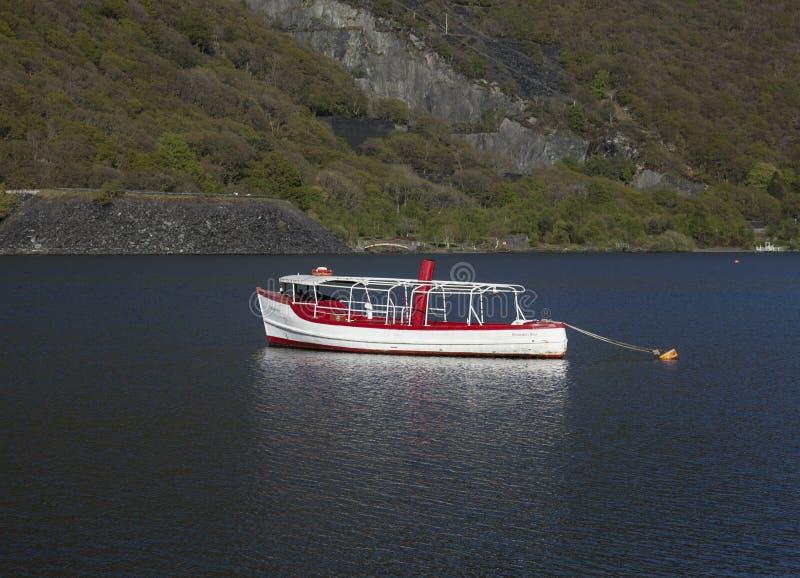 Llanberis, Nord-Wales - blaues Wasser von einem See und von weißen und roten Boot lizenzfreie stockbilder