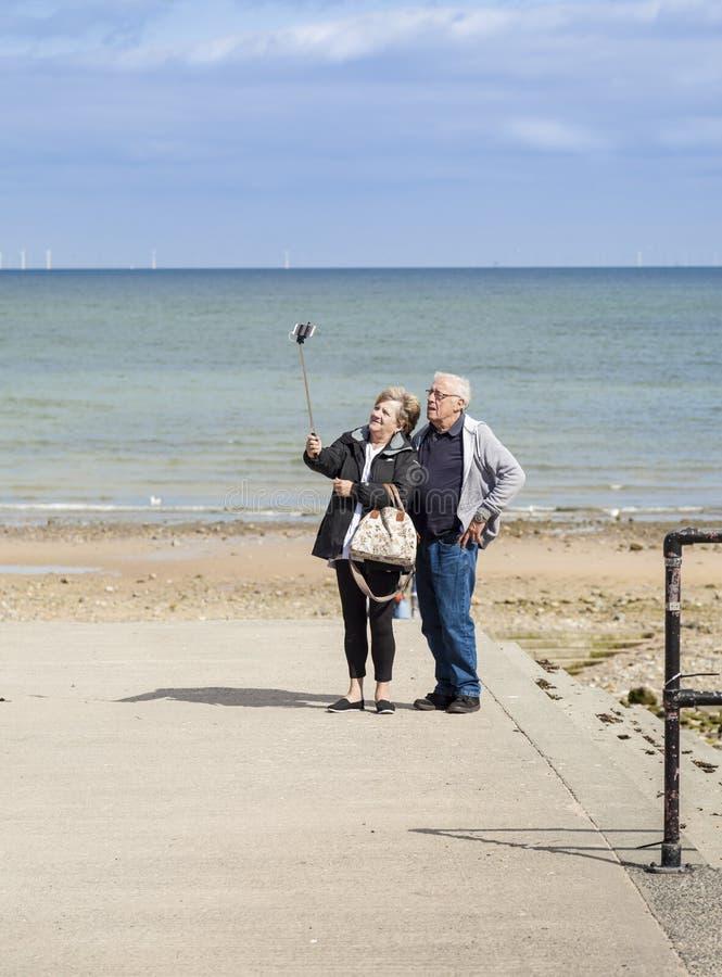 Llandudno, Pays de Galles, U K- 9 septembre 2015 : Touristes pluss âgé de femme d'homme prenant des selfies utilisant un appareil photographie stock libre de droits