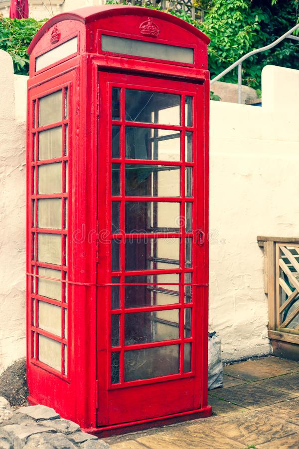 LLandudno, Wales, UK - MAY 27, 2018 An old classic British red phone booth. Traditional red phone box on street. Not working vinta. An old classic British red royalty free stock photography
