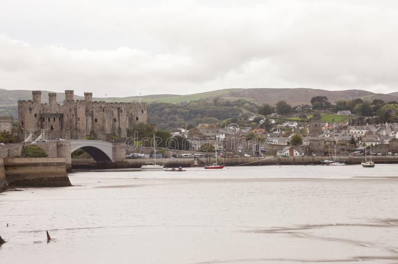 LLandudno, Wales, UK - MAY 27, 2018 River flowing beside the castle. Boats floating in the river. Bridge over the river. Castle on royalty free stock photography