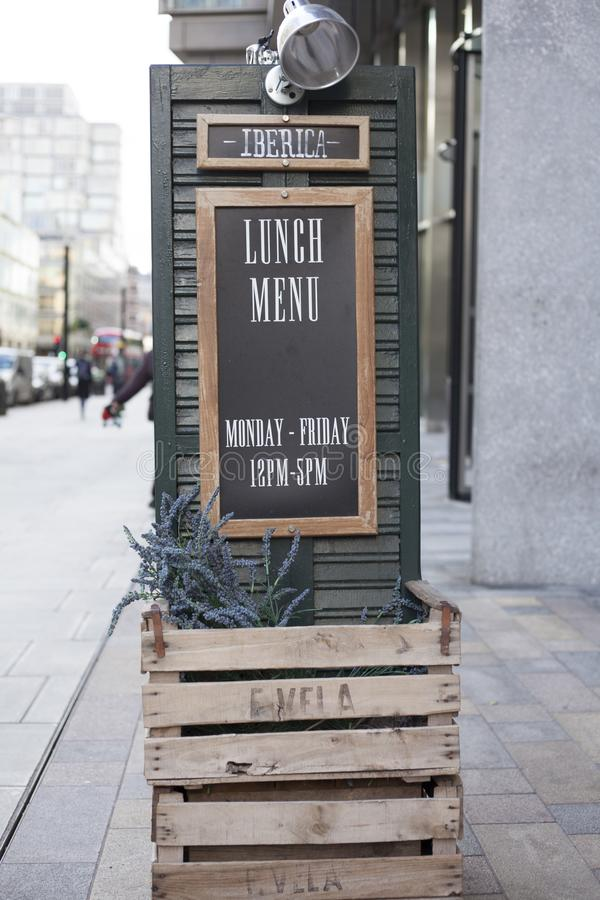 LLandudno, Wales, UK - MAY 27, 2018 Wooden black board outside the cafe. Large outdoor timings display of the resteraunt. Easle si stock image