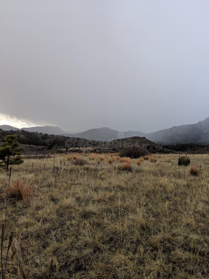 Llanos planos con las montañas en fondo, cielos oscuros imagenes de archivo