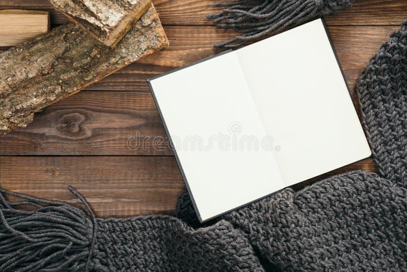 Llattabuch mit leerer Seite, graugestrickter Schal, Holzholz auf Holzhintergrund Flachlage, oberste Ansicht, Overhead Gemütliches stockfoto