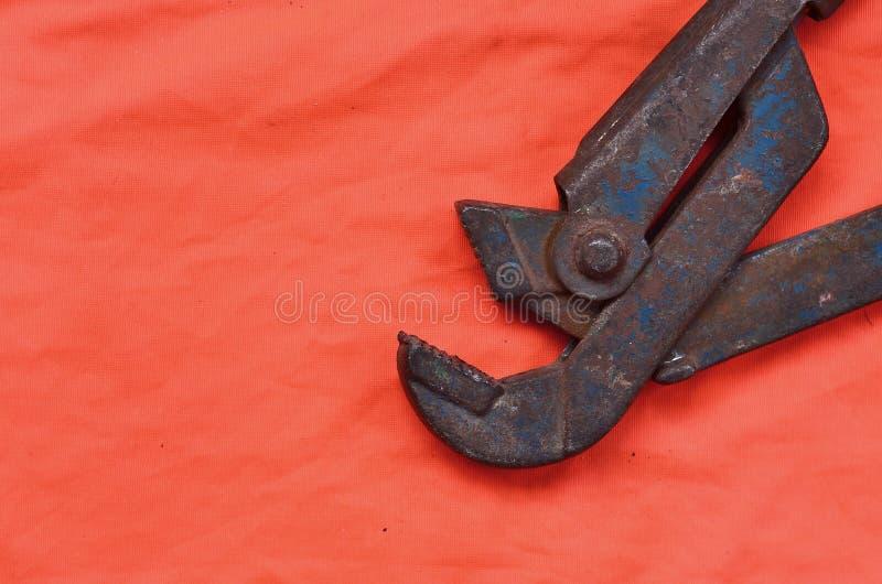 Llave ajustable contra la perspectiva de una camisa anaranjada del trabajador de la señal Todavía la vida se asoció a la reparaci foto de archivo