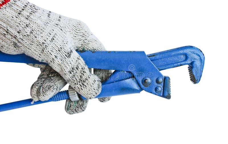 Llave ajustable del gas en la mano de un hombre en un guante de trabajo Herramienta del cerrajero imagen de archivo