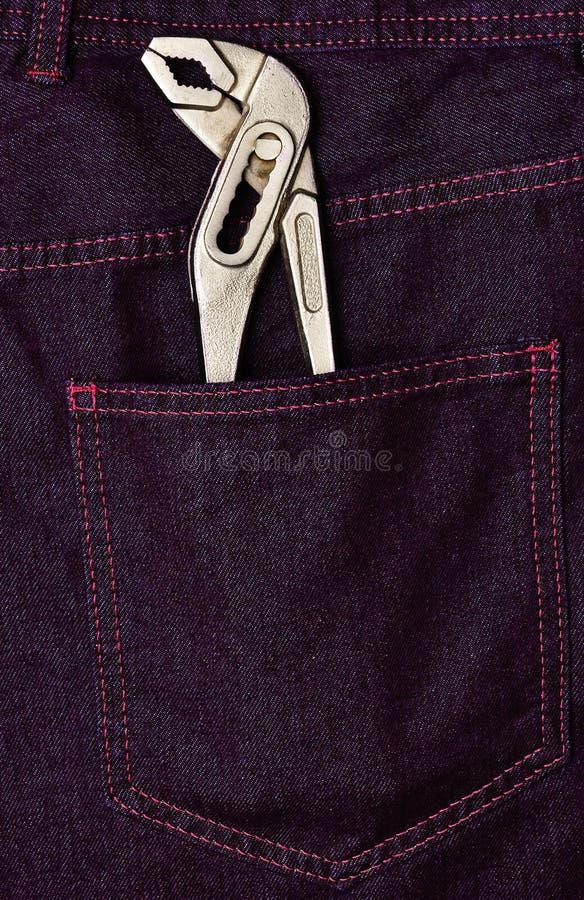 Llave ajustable en el bolsillo trasero de los vaqueros fotografía de archivo