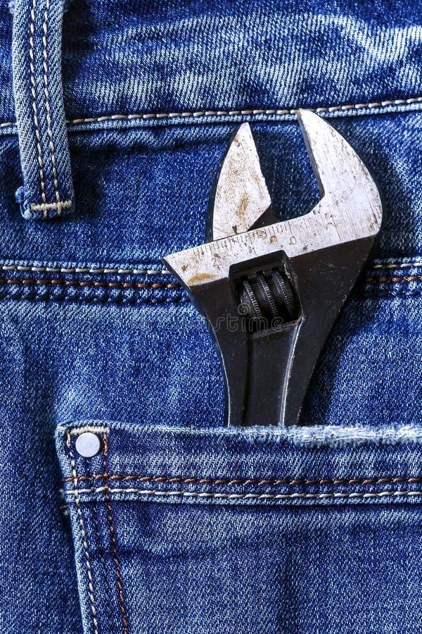 Llave ajustable en el bolsillo trasero de vaqueros del dril de algodón fotos de archivo libres de regalías
