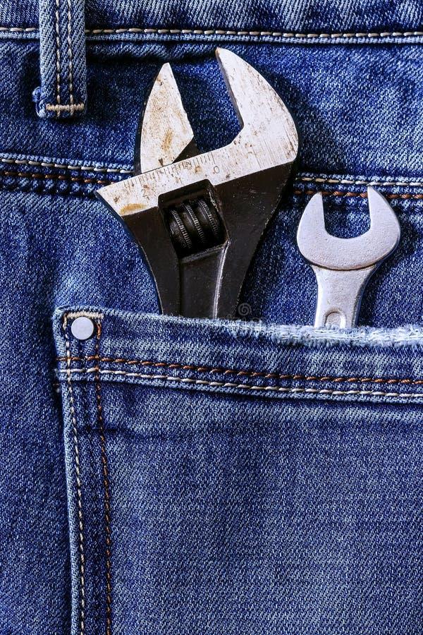 Llave ajustable en el bolsillo trasero de vaqueros del dril de algodón fotografía de archivo