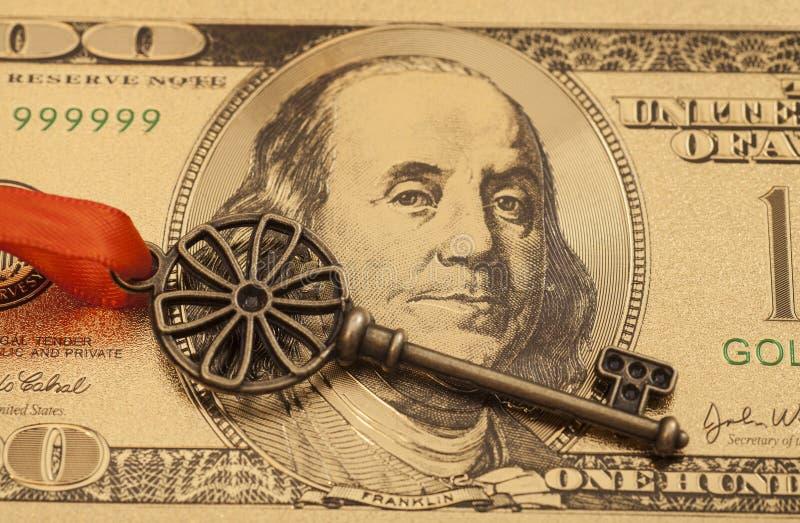 Llave al éxito con el arco rojo en cientos billetes de dólar de oro foto de archivo libre de regalías
