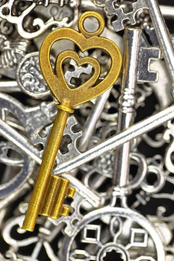 Llave antigua de oro en la pila de llaves metálicas imagen de archivo libre de regalías