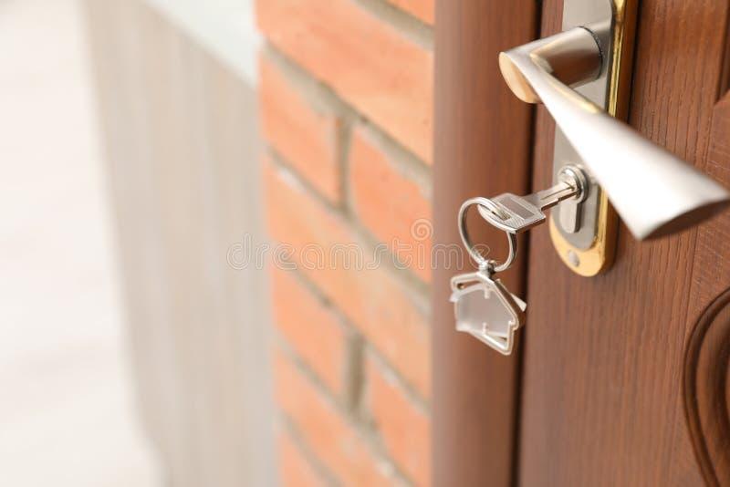 Llave con la baratija casa-formada en la cerradura de puerta, primer imagen de archivo