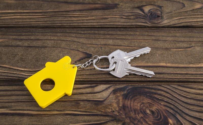 Llave con llavero formado amarillo de la casa en cadena en el fondo de madera de la textura imagenes de archivo