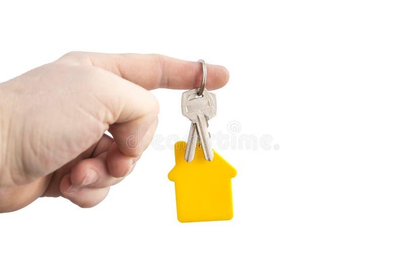Llave con una casa formada amarilla en una cadena en una mano en un fondo blanco imagenes de archivo