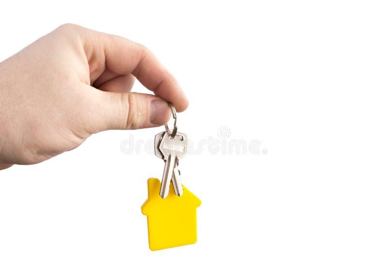 Llave con una casa formada amarilla en una cadena en una mano en un fondo blanco foto de archivo