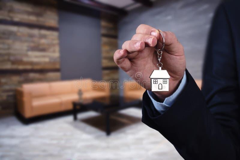 Llave confiada de la casa de la tenencia de la mano del hombre joven, agente inmobiliario foto de archivo