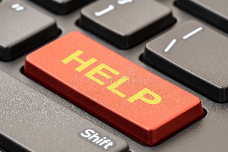 Llave de ayuda en un teclado negro fotos de archivo