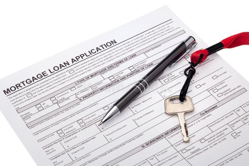 Llave de la casa con el uso de préstamo de hipoteca foto de archivo