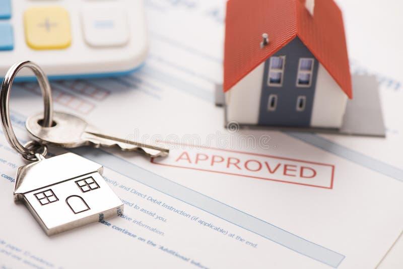 Llave de la casa con el uso de préstamo de hipoteca imagen de archivo