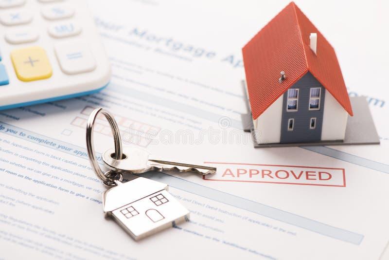 Llave de la casa con el uso de préstamo de hipoteca imagenes de archivo
