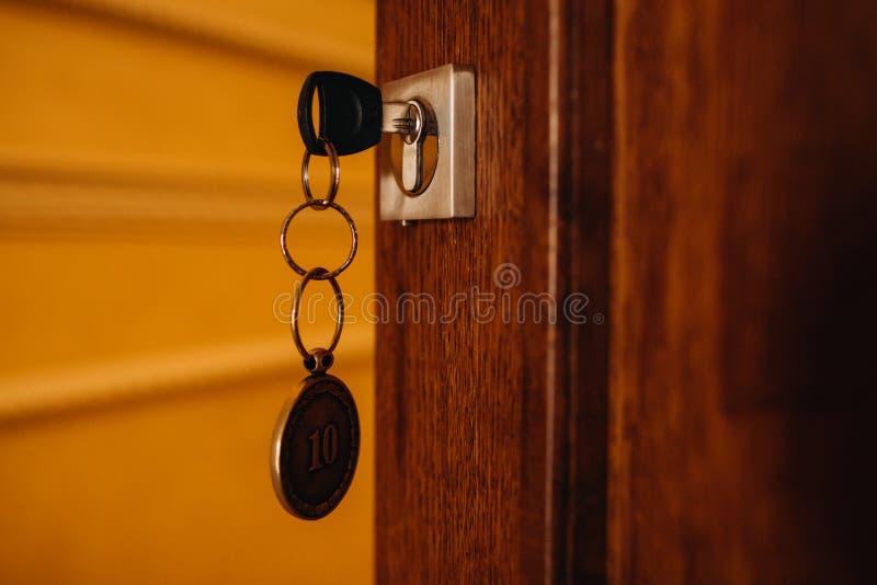 Llave de la casa en la puerta La llave con el llavero abre o cierra la puerta de madera fotos de archivo libres de regalías