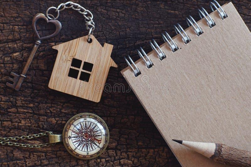 Llave de la forma del llavero y del corazón de la casa dispuesta así como el cuaderno antiguo del compás y del papel en la tabla  imagenes de archivo