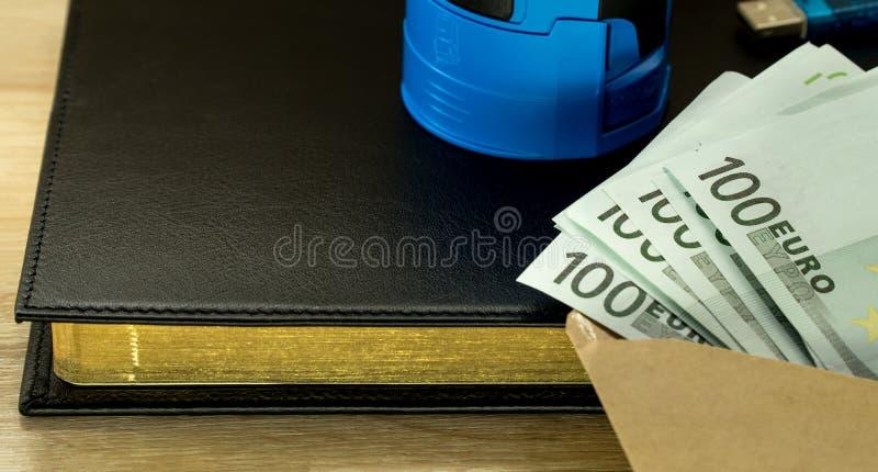 Llave de la seguridad del usb del dinero en sobre en la libreta negra del fondo foto de archivo