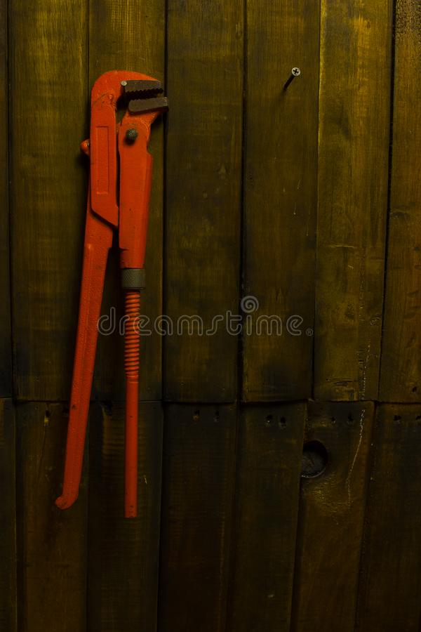 Llave de tubo anaranjada vieja que cuelga en la pared de madera foto de archivo libre de regalías