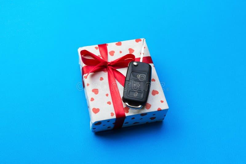 Llave del coche en la caja de regalo de papel con el arco rojo de la cinta y corazón en fondo azul de la tabla Los días de fiesta imágenes de archivo libres de regalías