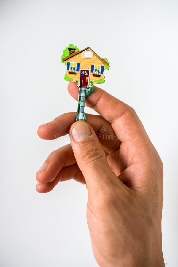 Llave en la forma de una casa en la mano en el fondo blanco foto de archivo libre de regalías