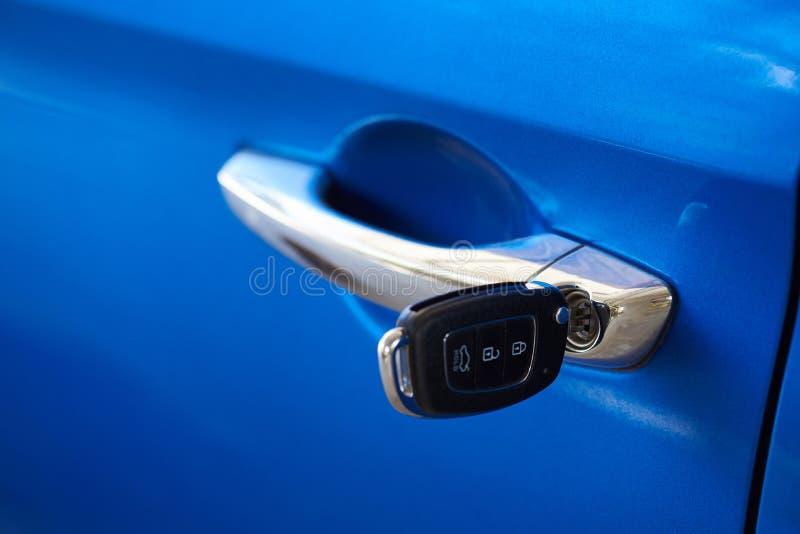 Llave negra del coche en coche azul foto de archivo libre de regalías