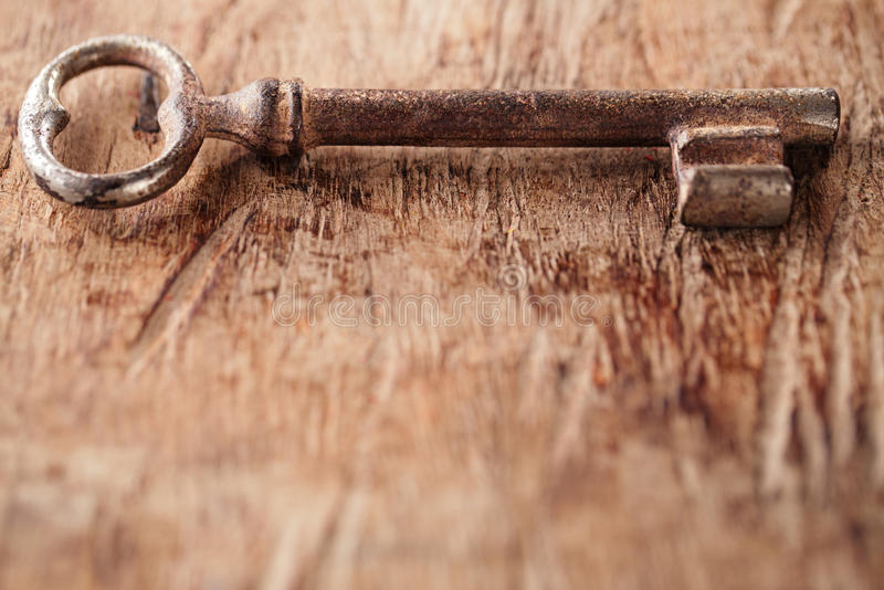 Llave oxidada grande del metal del vintage en viejo fondo de madera imagenes de archivo