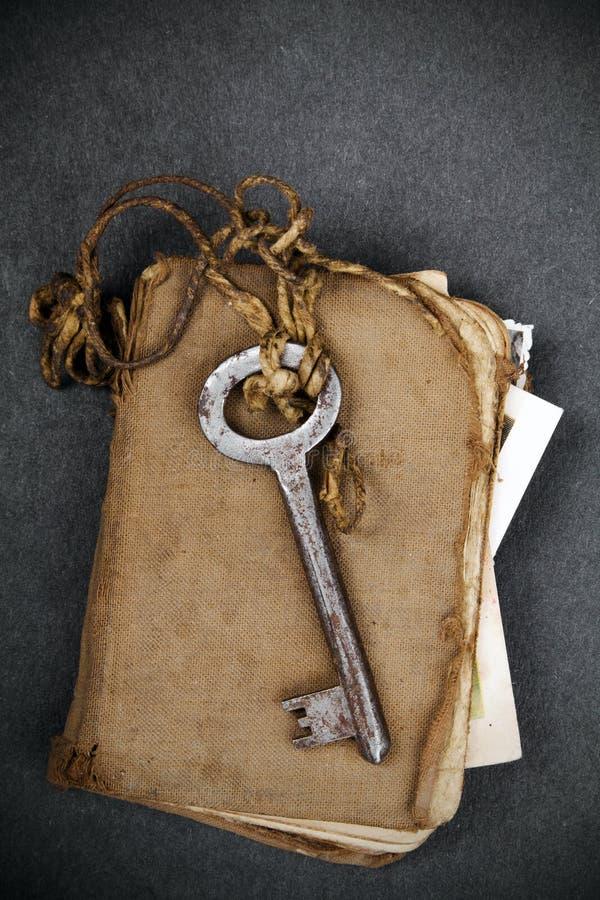 Llave oxidada, libro viejo y fotografía vacía como metáfora de las memorias foto de archivo