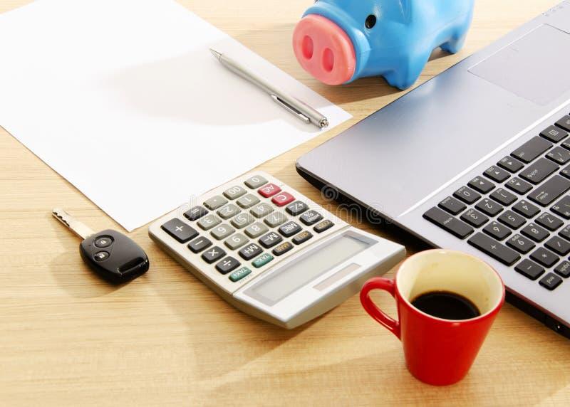 Llave y calculadora del coche con los materiales de oficina en el escritorio de madera de la tabla fotos de archivo