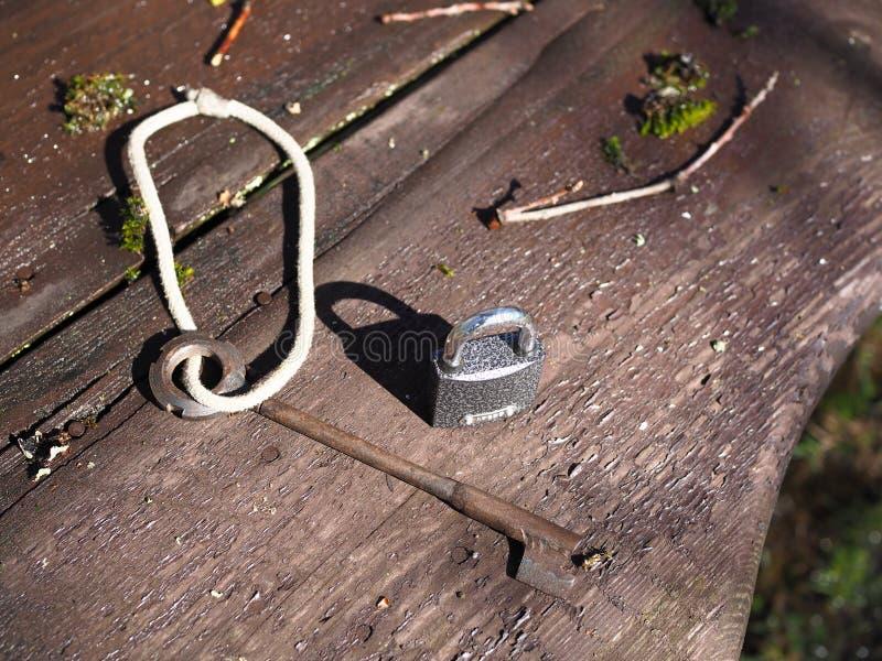 Llave y cerradura en un banco de madera en el bosque imagenes de archivo