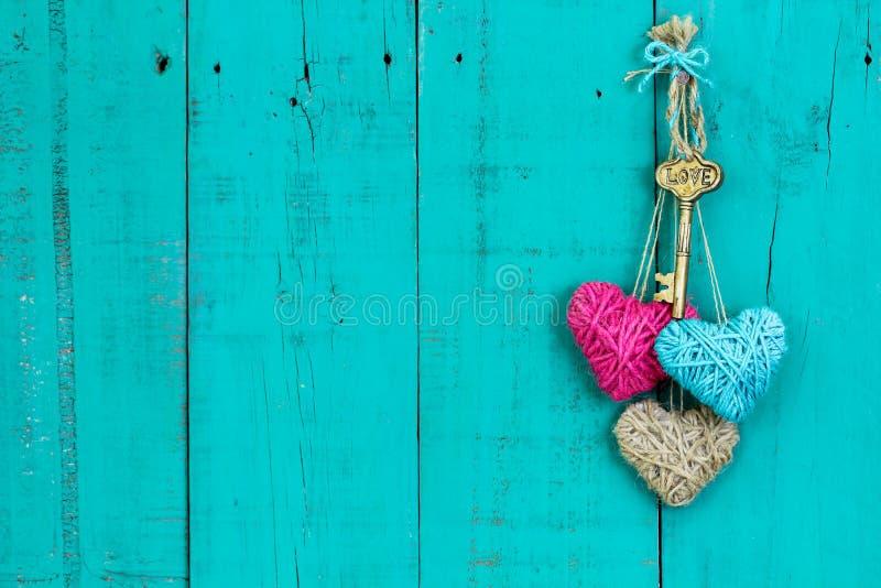 Llave y corazones que cuelgan en la puerta de madera fotografía de archivo libre de regalías