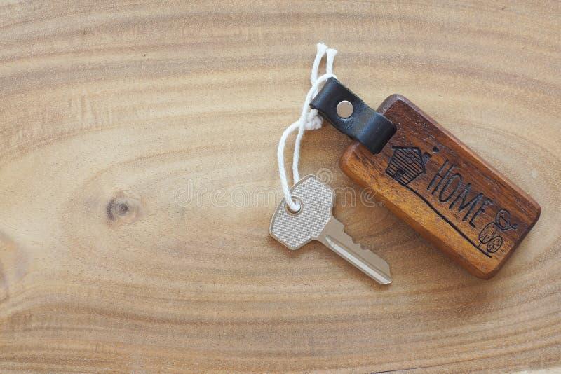 Llavero casero de madera con la llave maestra de la casa en piso de madera ligero Recepción al nuevo concepto casero Copie el esp fotos de archivo