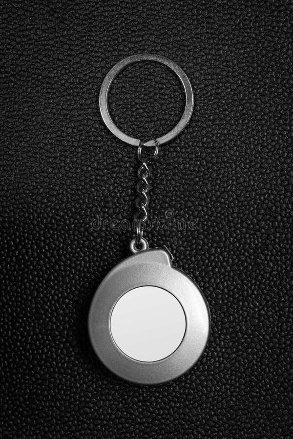 Llavero de acero en fondo de cuero oscuro Llavero en blanco en concepto de la cinta m?trica imagenes de archivo