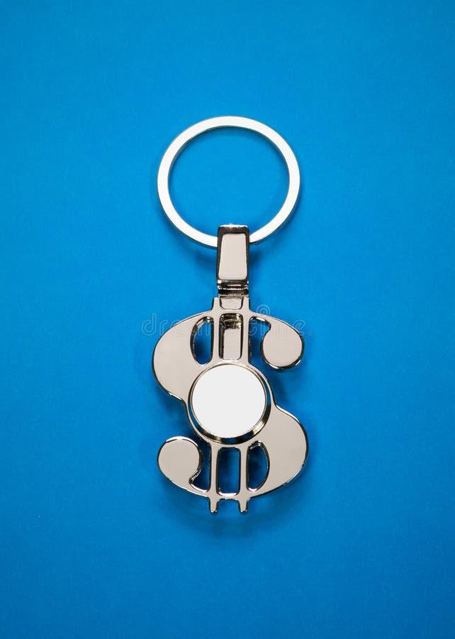 Llavero de acero en fondo de papel azul Llavero o complemento en blanco para su diseño Puede poner el texto, la imagen, y el logo fotografía de archivo