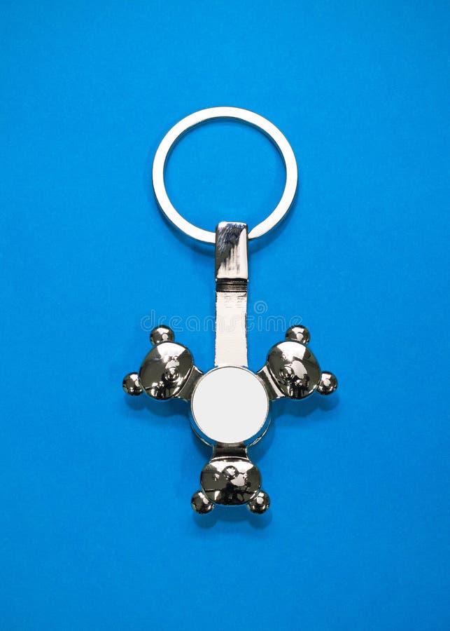 Llavero de acero en fondo de papel azul Llavero o complemento en blanco para su diseño Puede poner el texto, la imagen, y el logo foto de archivo