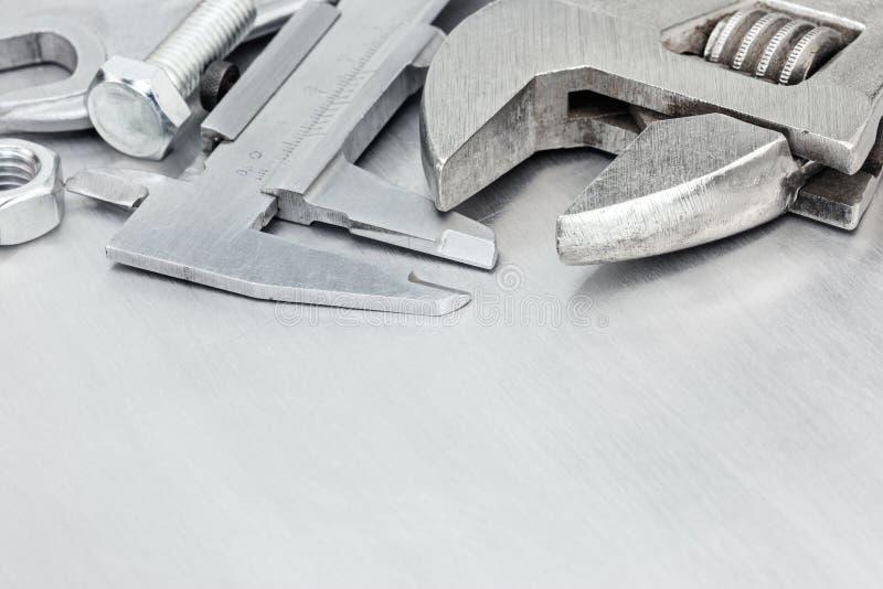 Llaves, calibrador, tornillos en fondo rasguñado de la superficie de metal imágenes de archivo libres de regalías