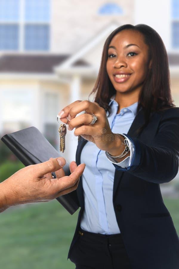 Llaves de entrega del agente inmobiliario imagen de archivo