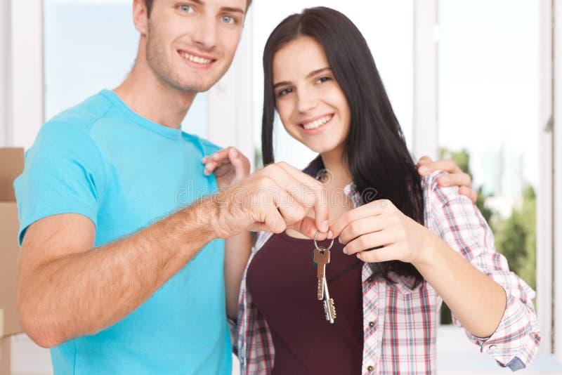 Llaves de su nueva casa Pares jovenes alegres que llevan a cabo llave fotografía de archivo