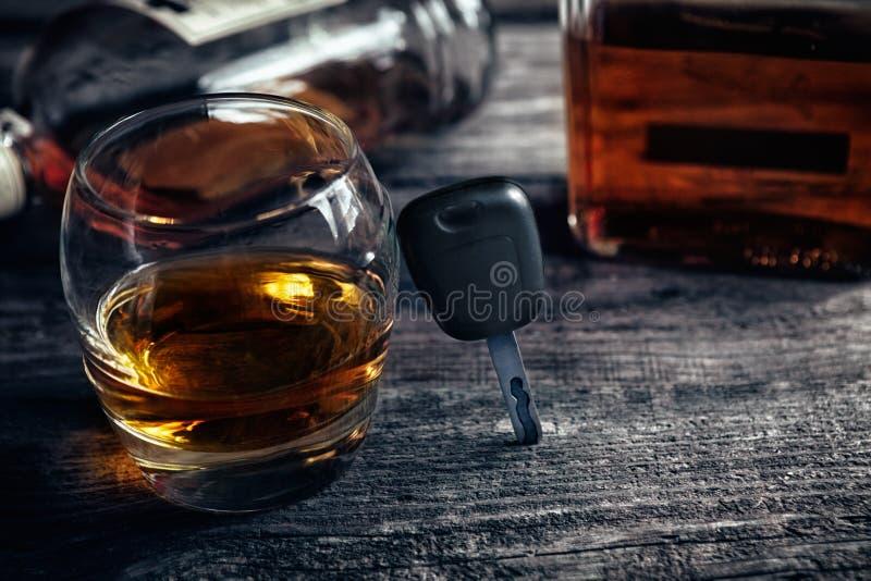 Llaves del coche del automóvil sobre el vidrio con el whisky imagen de archivo
