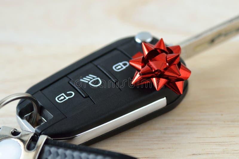 Llaves del coche con el arco rojo del regalo - concepto de nuevo regalo del coche imagenes de archivo