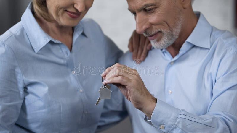 Llaves masculinas mayores de la casa de la tenencia, señora que sonríe, inversión de la compra de las propiedades inmobiliarias fotos de archivo