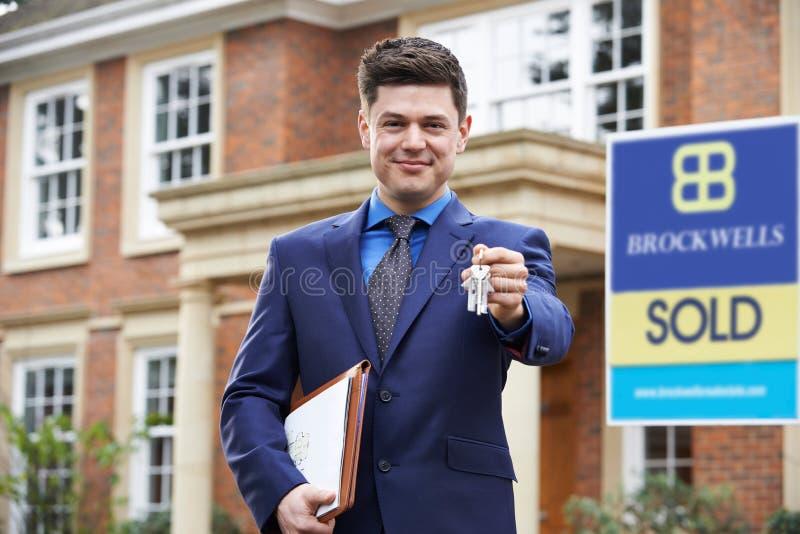 Llaves residenciales de la tenencia de propiedad del exterior derecho masculino del agente inmobiliario imagenes de archivo