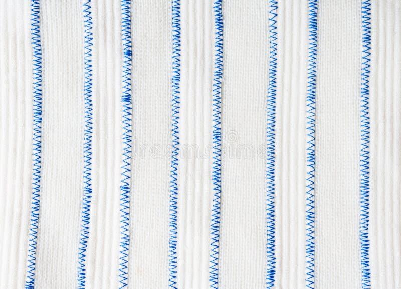 Lle bande bianche verticali di due tessuti differenti sono collegate da un punto blu di zigzag fotografia stock