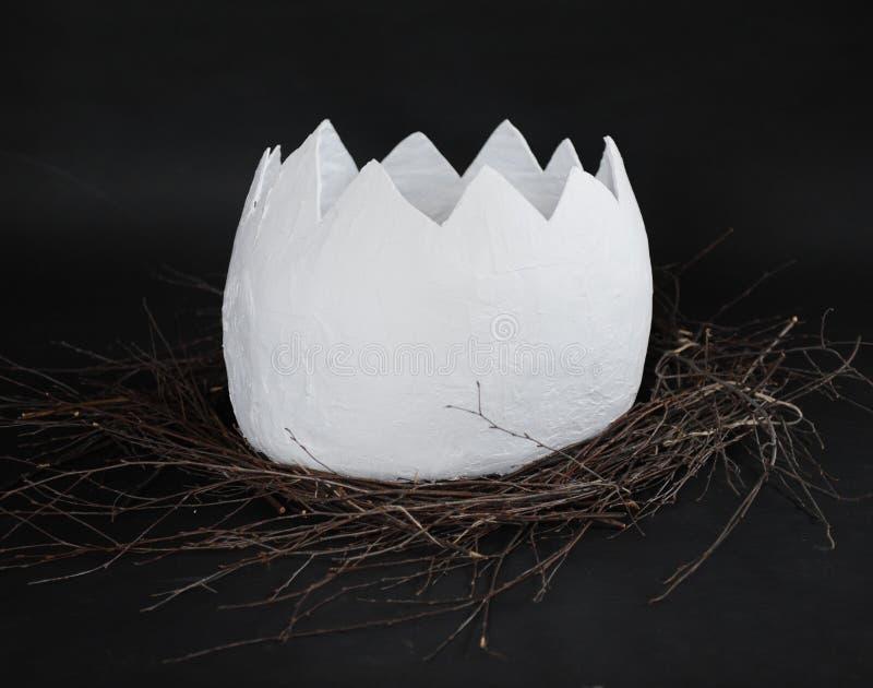 Lle coperture di un uovo enorme della cartapesta in un nido dei rami su un fondo nero immagini stock